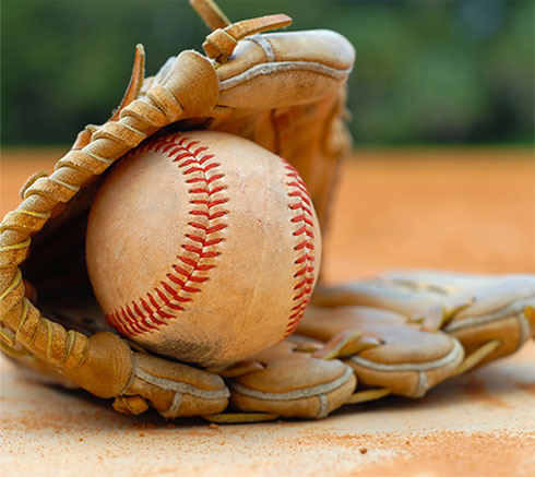 baseball glove on ground holding baseball